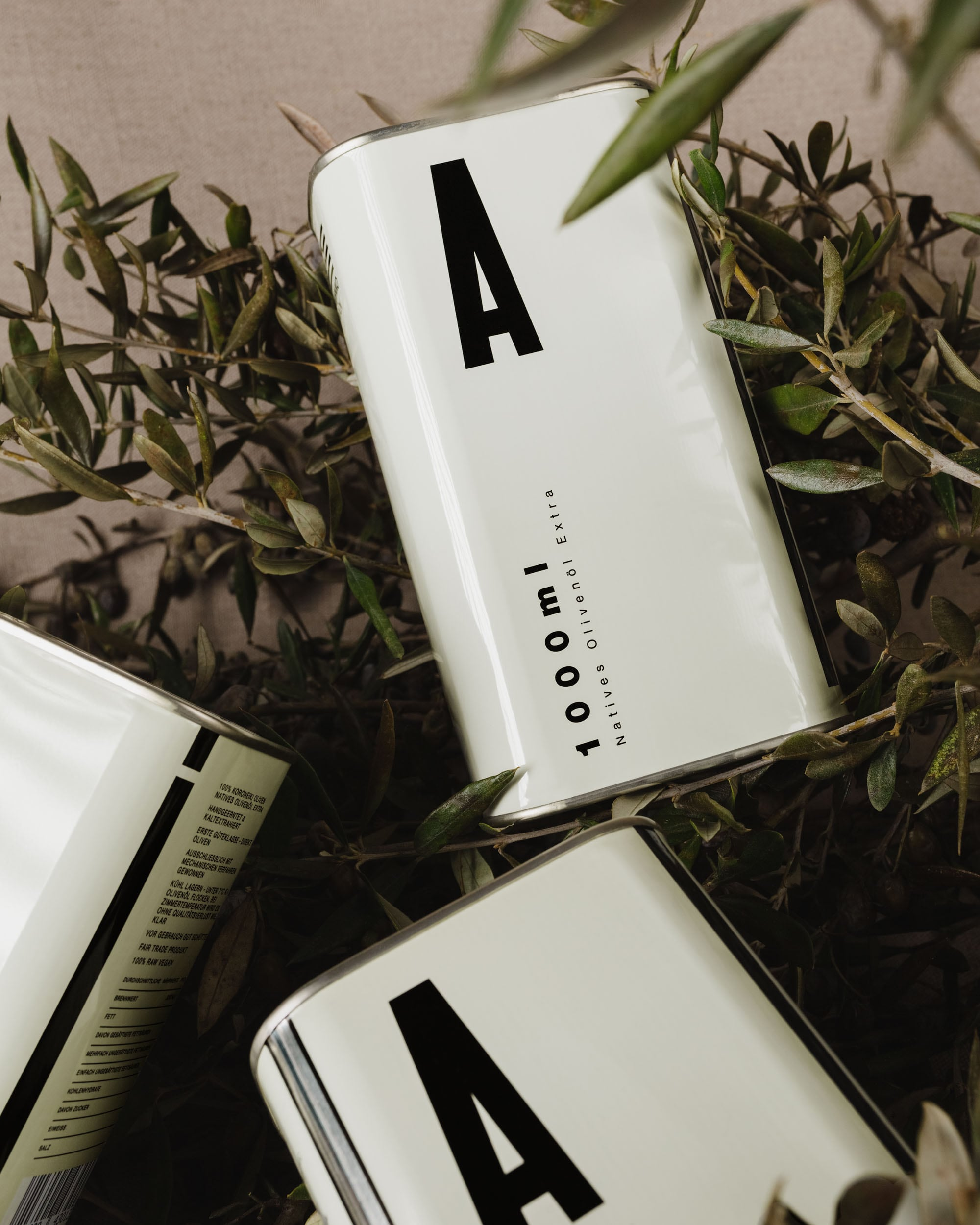 Three 1000ml A! canisters on a bed of olive branches.
