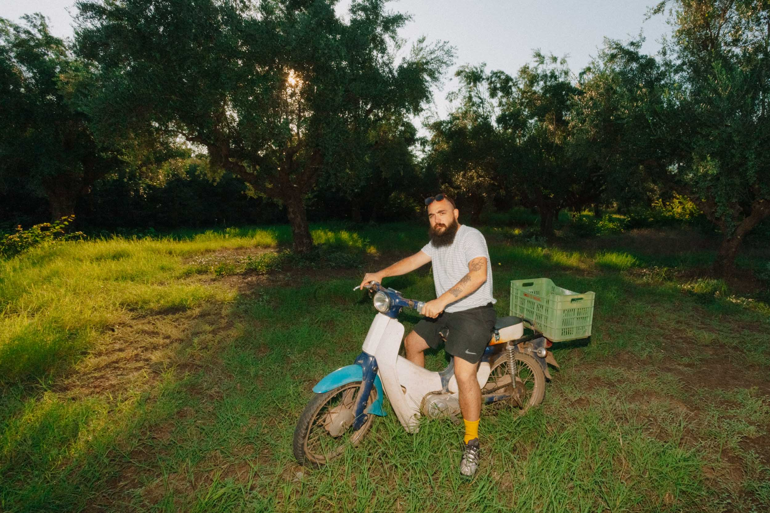 Simone on a moped in the olive grove.